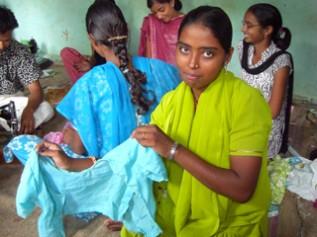 縫製の職業訓練を受けて自分で縫ったサリーを見せくれるインドの女の子