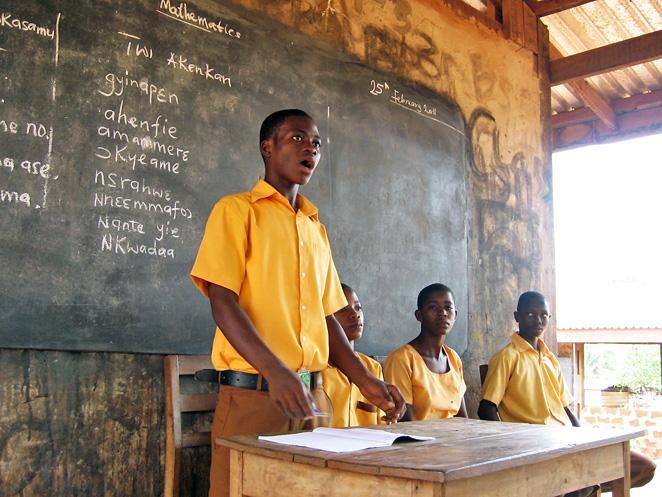 村の学校でみんなの前に立ち発表するゴッドフレッドくん