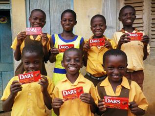 売上の一部で支援した地区の子どもたちにDARSを持ってもらって記念写真