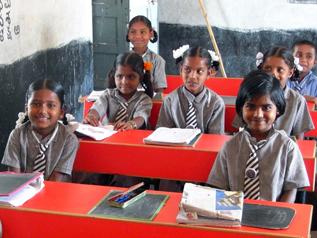 公立学校に新しく揃えられた赤い机で勉強する子どもたち