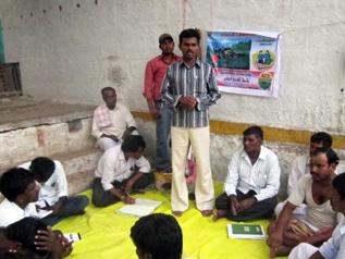 訪問先の住民が村や活動について説明