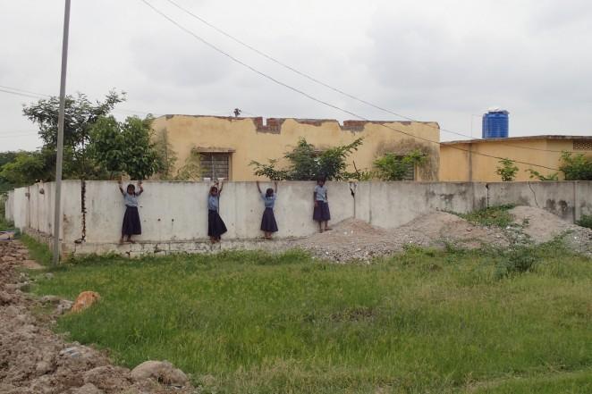 学校の裏で遊ぶ学校に通う子どもたち