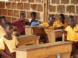 制服もなく教室の一番後ろで授業を受ける14歳の子ども
