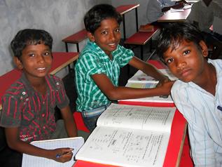 新しい机と椅子で勉強するインドの子どもたち