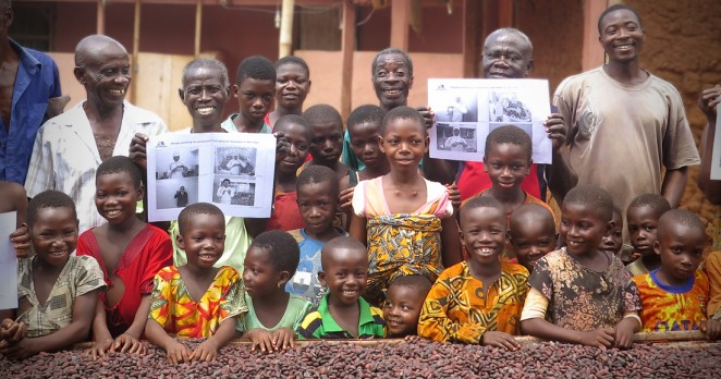 ACEが支援するカカオ生産地の農家と子どもたち(日本から持参した森永製菓社員の写真を持って記念撮影)