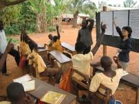 教室が足らず、屋外で授業を受けている子どもたちも