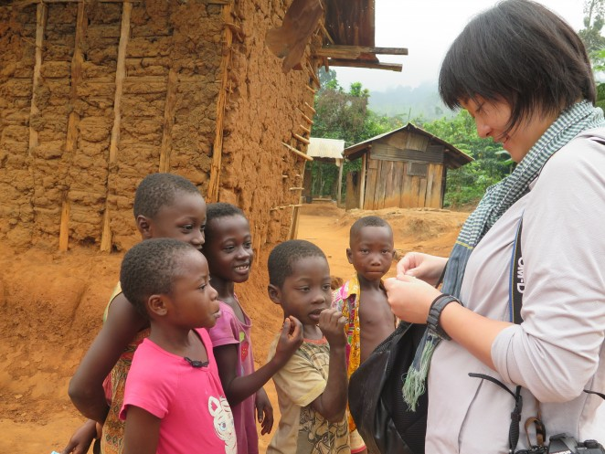 村の子どもたちに折り紙を折る安田菜津紀さん(右)
