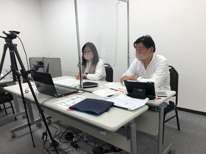 総会の議長を務めた理事小林(右)と議案を説明する代表岩附(左)